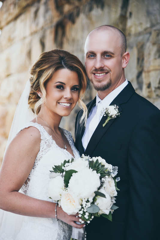 smiling photo of bride and groom in front of a stone wall