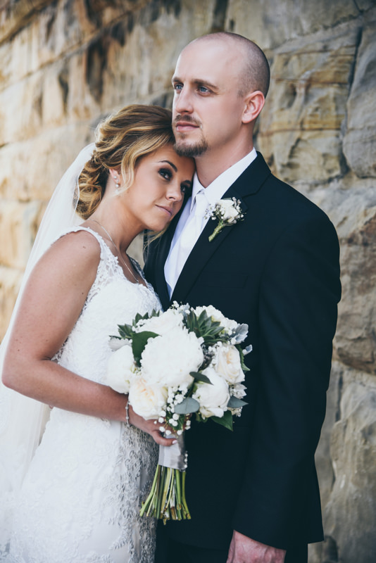 image of a groom leaning into his bride in front of a stone wall