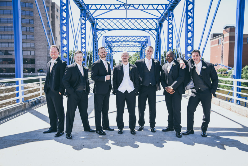 groom and groomsmen in black tuxes on a blue bridge