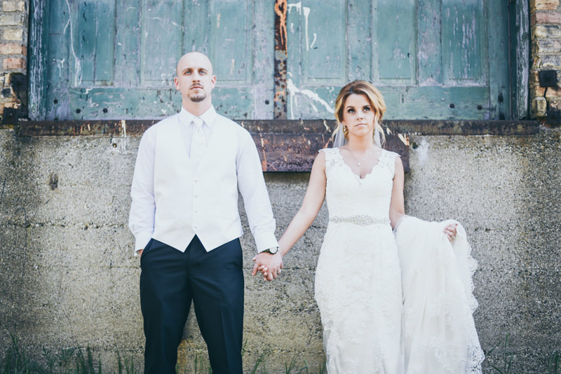 a bride and groom holding hands in front of old teal warehouse doors
