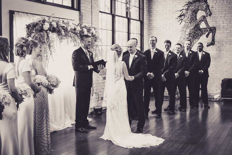 black and white image of bride and groom and groomsmen at the altar during wedding ceremony