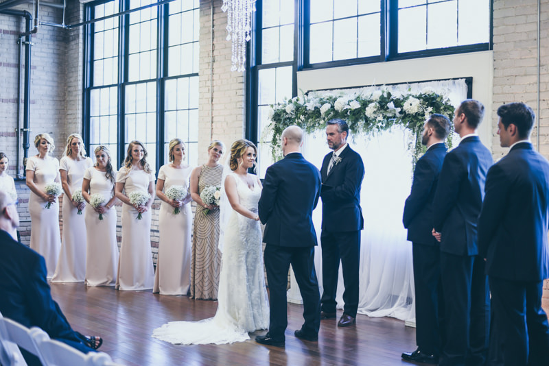 bride and groom and bridesmaids at the altar during a wedding ceremony