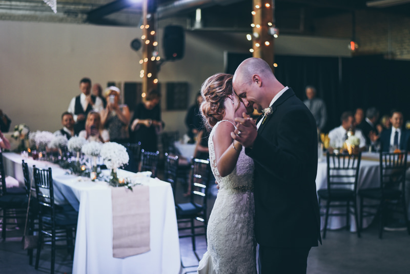 bride and grooms first dance under a crystal chandelier in an old loft wedding venue