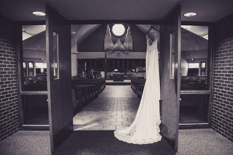 black and white image of a brides gown hanging in the entry of a church sanctuary