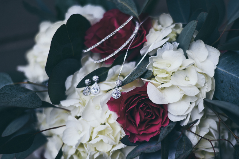 bridal bouquet of burgundy roses and white hydrangeas with greenery and bridal jewelry