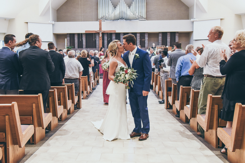 bride and groom kissing in the middle of the aisle after their wedding ceremony