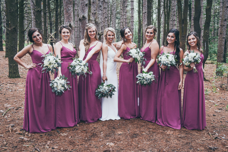 bridal party in magenta and navy in a pine forest for photos