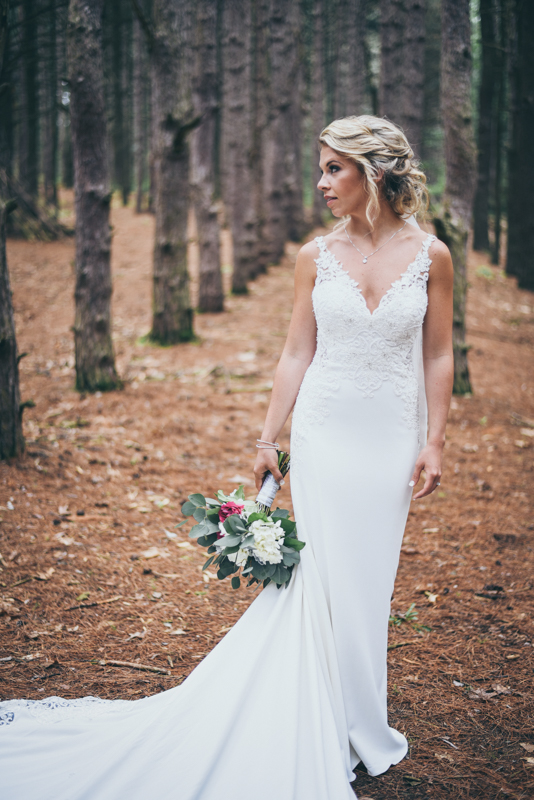 bride standing in a pine forest