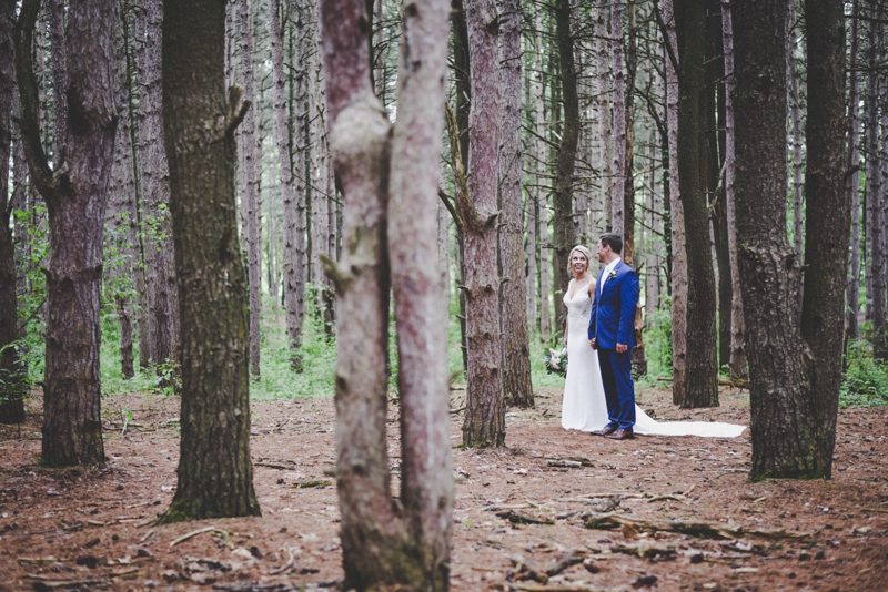 bride and groom walking away in a pine forest