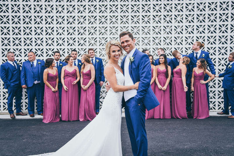 bridal party in navy and magenta in front of a geometric brick wall in grand rapids michigan