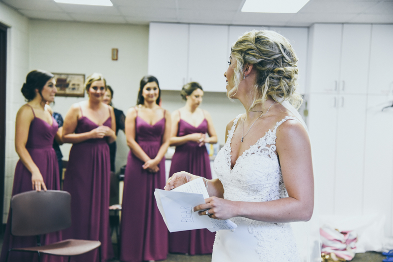 a bride reading her letter from her groom as her bridesmaids watch