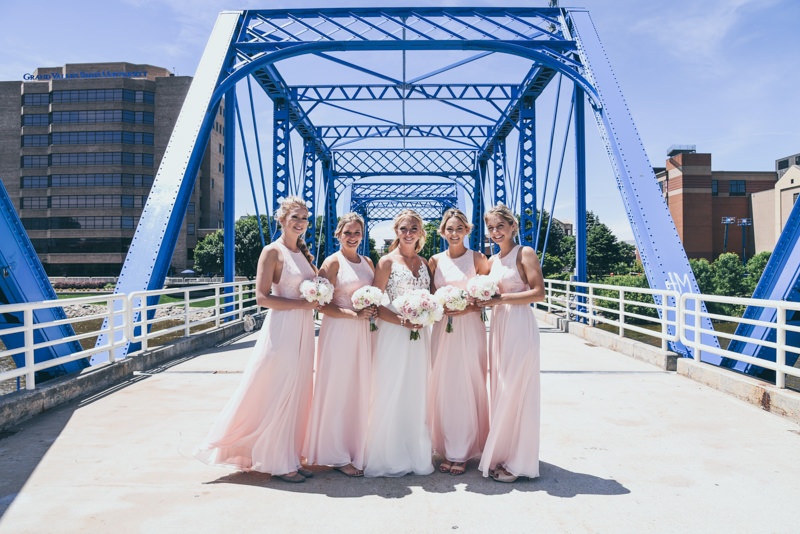 brides and bridesmaids in pink dresses on the blue bridge in grand rapids mi