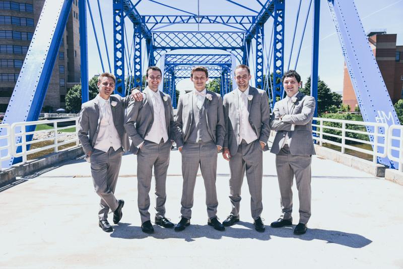 groomsmen in sandstone allure tuxedos on the blue bridge in grand rapids mi