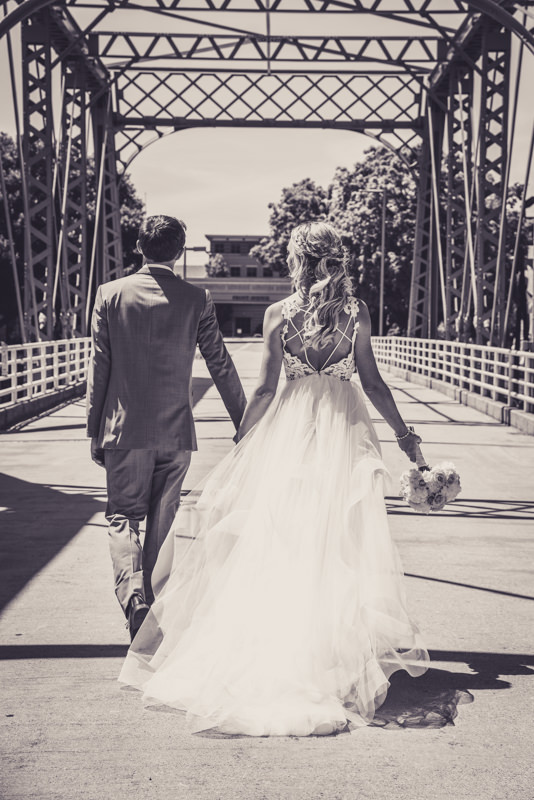black and white image of a bride and groom walking away on a bridge