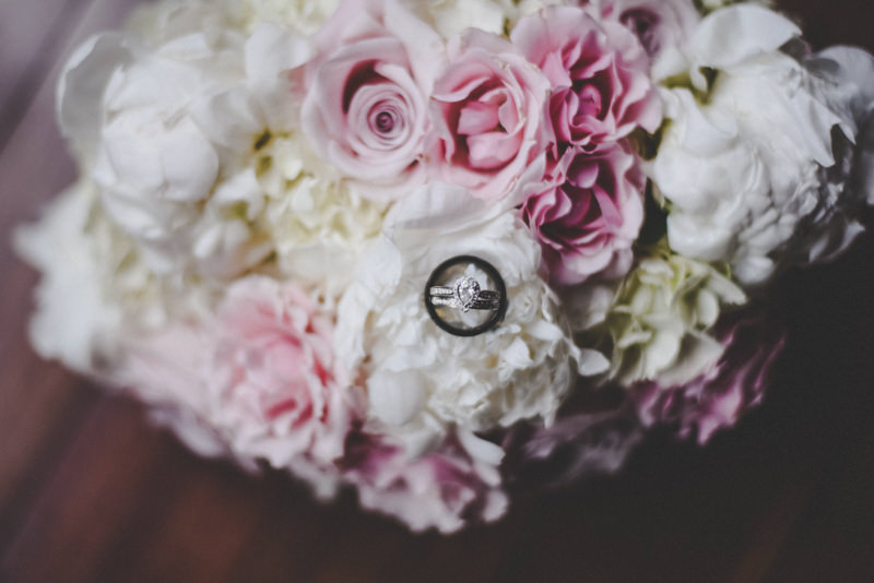 bridal bouquet of white hydrangeas, pink roses and white flowers with wedding rings