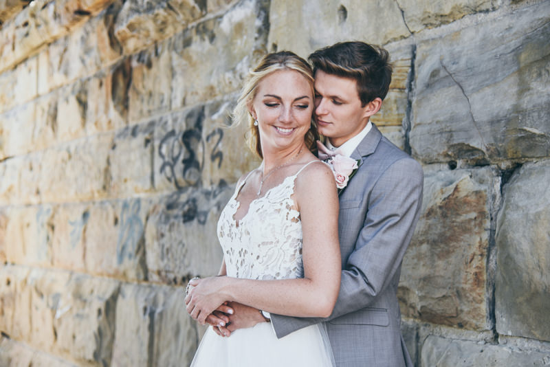 groom holding his bride against a stone wall