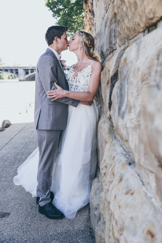 bride and groom holding each other against a stone wall
