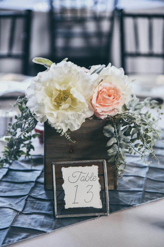 fresh flowers in a wooden cube with a gray table runner