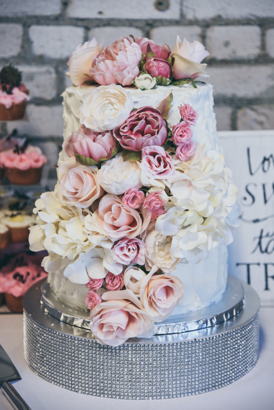 wedding cake with flowers of dark pink, light pink and cream