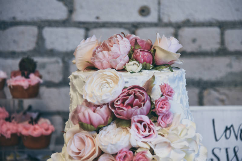 wedding cake with dark pink, light pink, and cream roses