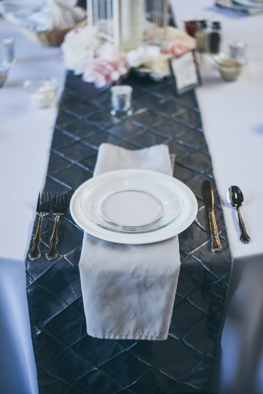table setting on a gray runner with a white lanter and fresh flowers