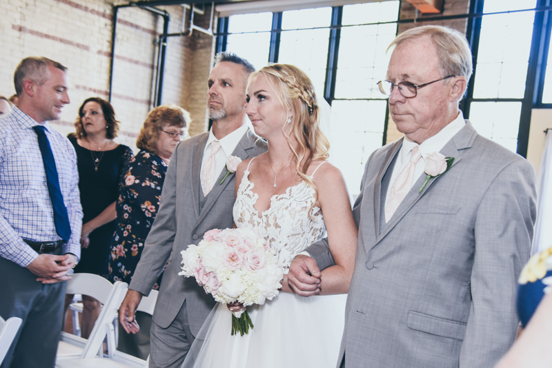 a dad and grandpa walking a bride down the aisle