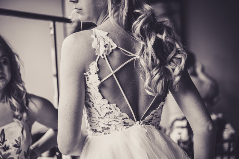 black and white detail image of the back of a laced up wedding dress