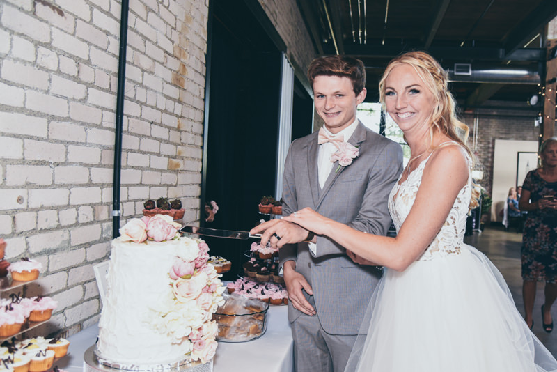 bride and groom smiling while they cut their cake