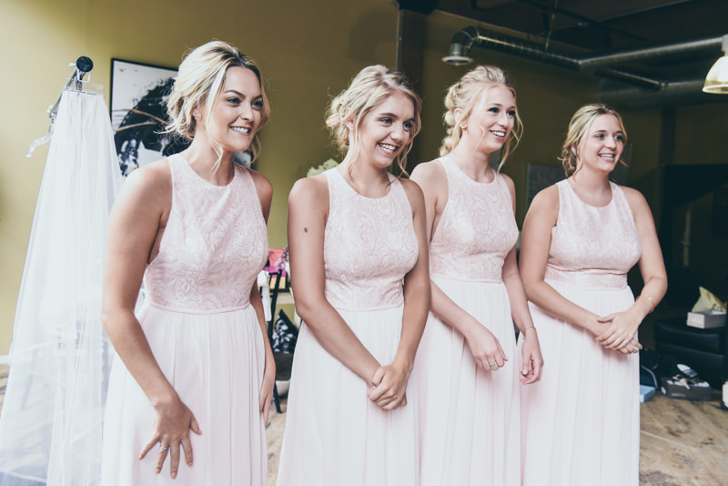 bridesmaids in pink dresses waiting for bride to come out of dressing room