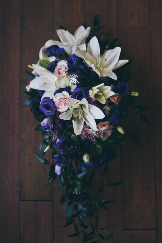 gorgeous cascading wedding bouquet with lilies and purple flowers