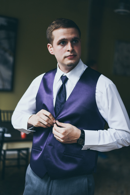 groom fastening his purple vest