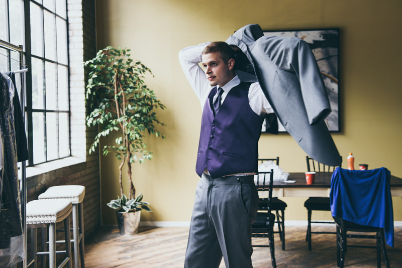 groom putting on a gray jacket over a purple vest