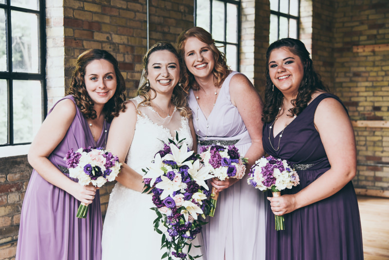 close up photo of a bride in white and her bridesmaids in varying shades of purple