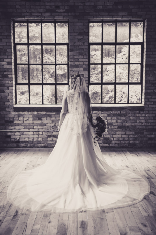 black and white image of a bride in an industrial loft