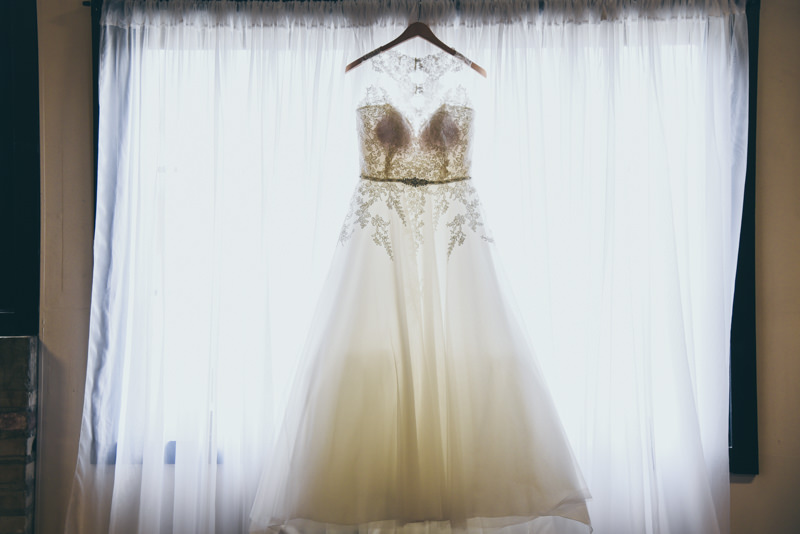 bridal gown hanging in a large window, backlit from the bright sunlight
