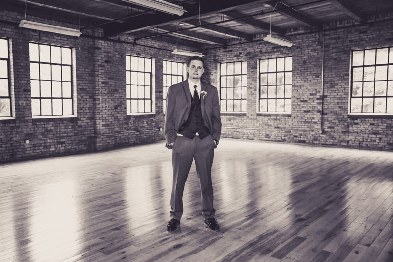 a black and white image of a groom in an industrial loft