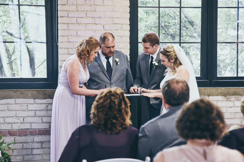 bride, groom, and witnesses signing the marriage license during the ceremony