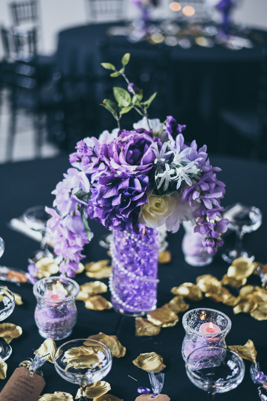 purple and gold floral centerpieces at a loft venue wedding reception