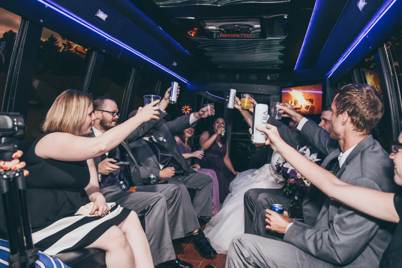 bridal party toasting the bride and groom on the party bus