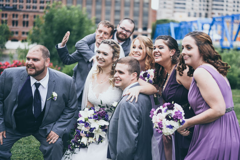 bridal party surrounding the bride and groom while everyone laughs