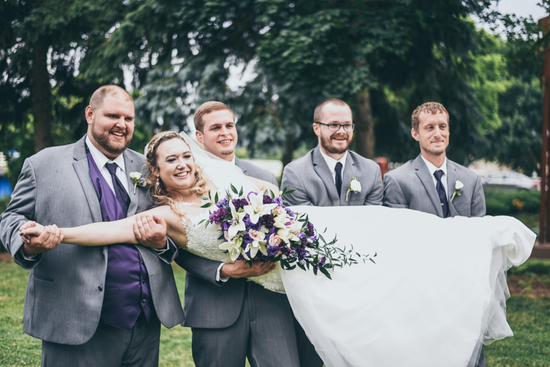 groomsmen holding up the bride and laughing