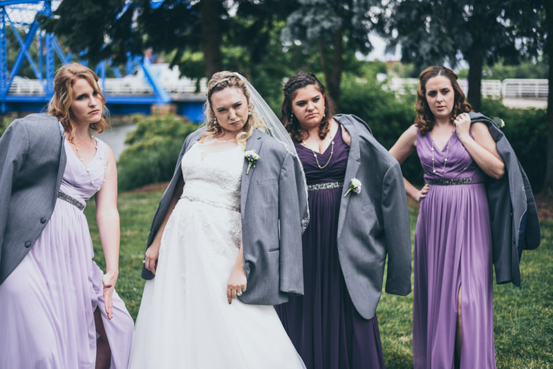 bride and bridesmaids wearing the guy's jackets and being silly