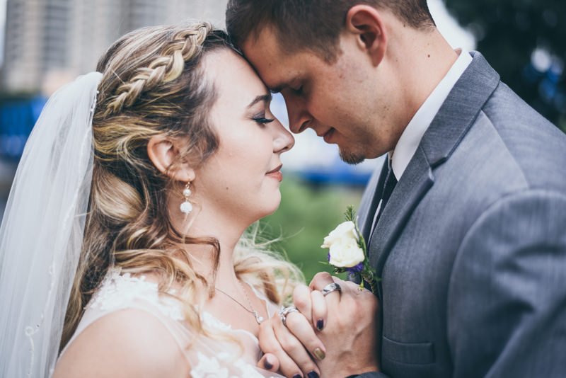Bride and Groom touching foreheads, holding hands, with closed eyes