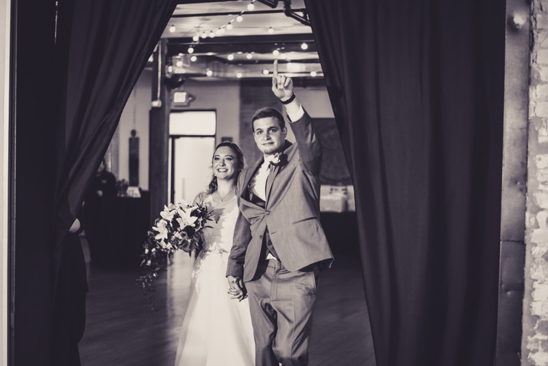 black and white photo of a bride and groom's grand entrance into their reception