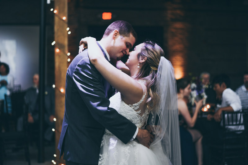 a bride and groom's first dance underneath a cascading chandelier in an industrial loft wedding venue