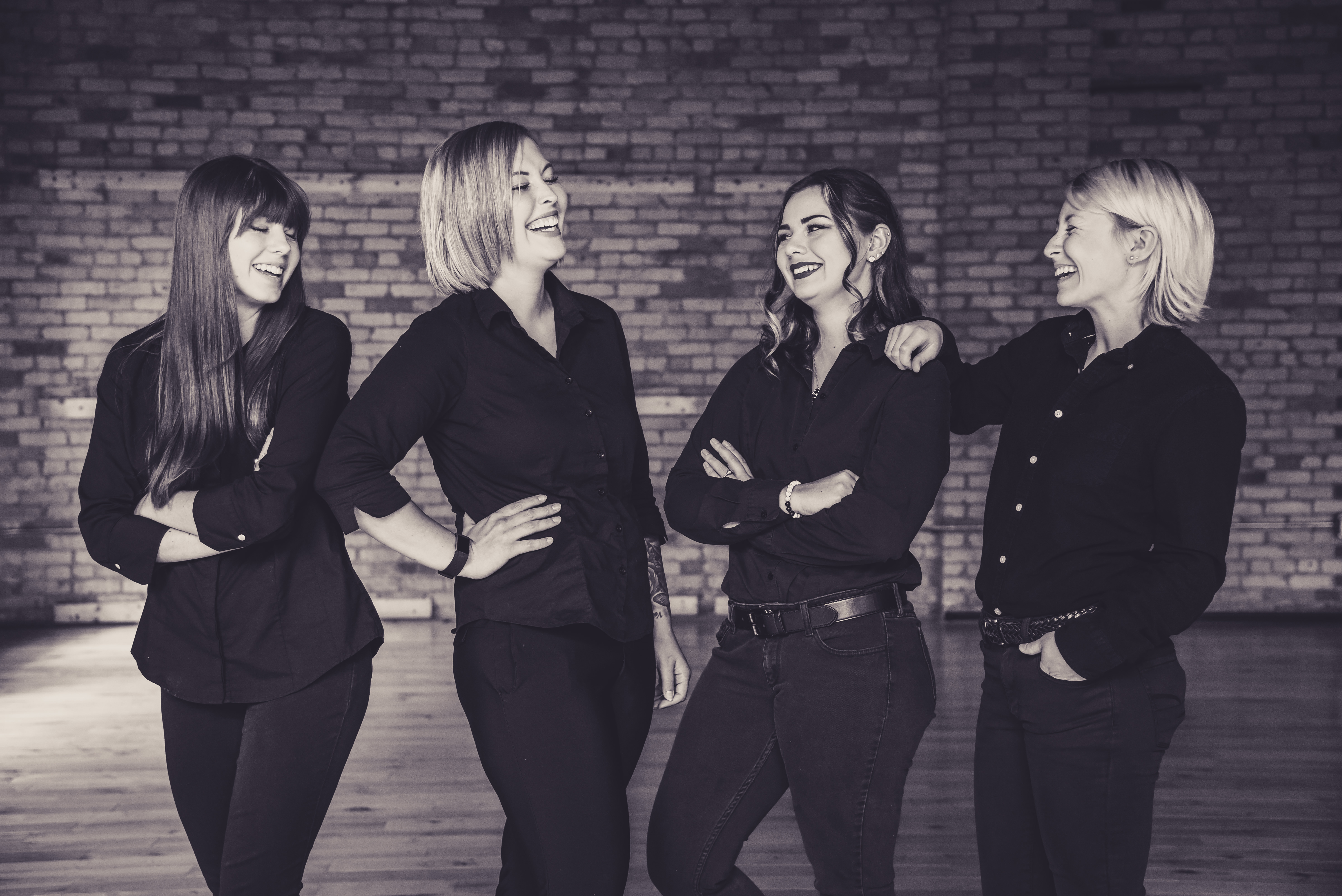 image of four women in black clothing in a brick building