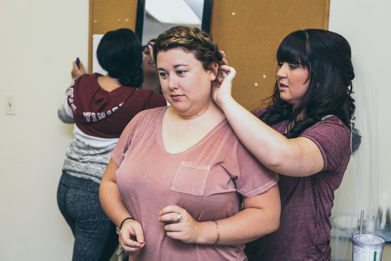 bride helping bridesmaid get ready before ceremony