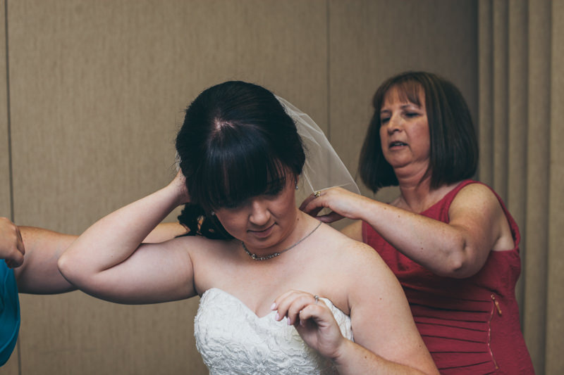 mother helping bride put on her wedding jewelry