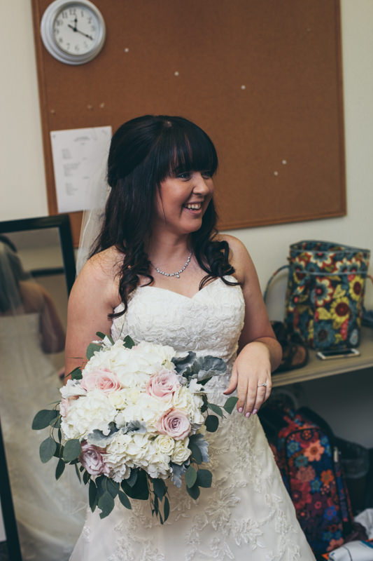 bride ready for ceremony, laughing in dressing room