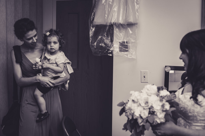 black and white image of bridesmaid and flower girl looking at the bride